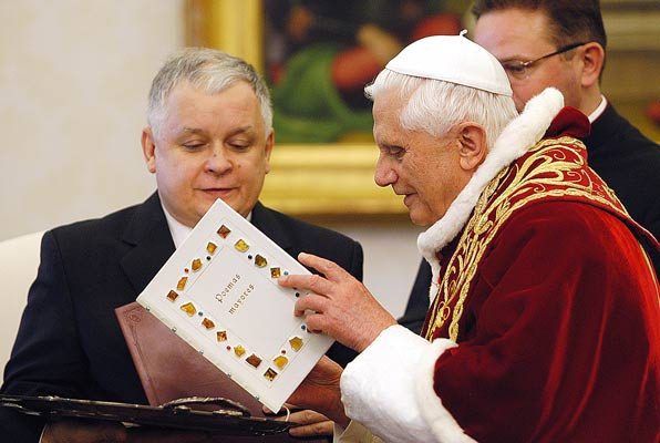 Polish president Lech Kaczynski gives as a gift art book published for the occasion